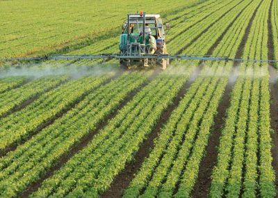 Farming tractor spraying a field